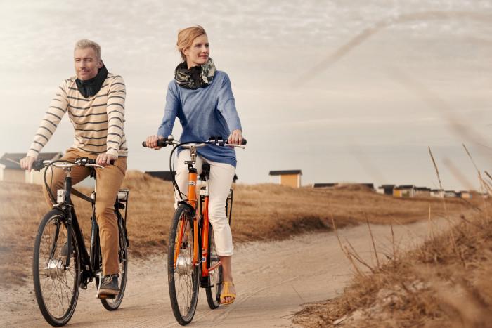 Due ciclisti che pedalano indossando l'Hovding
