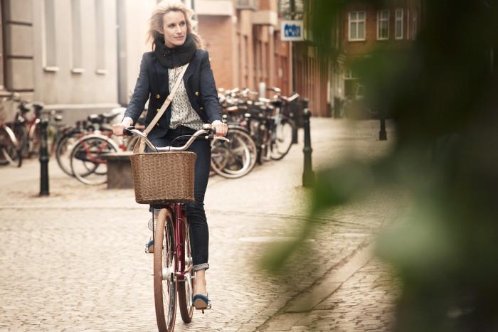 Una ciclista che pedala indossando l'Hovding