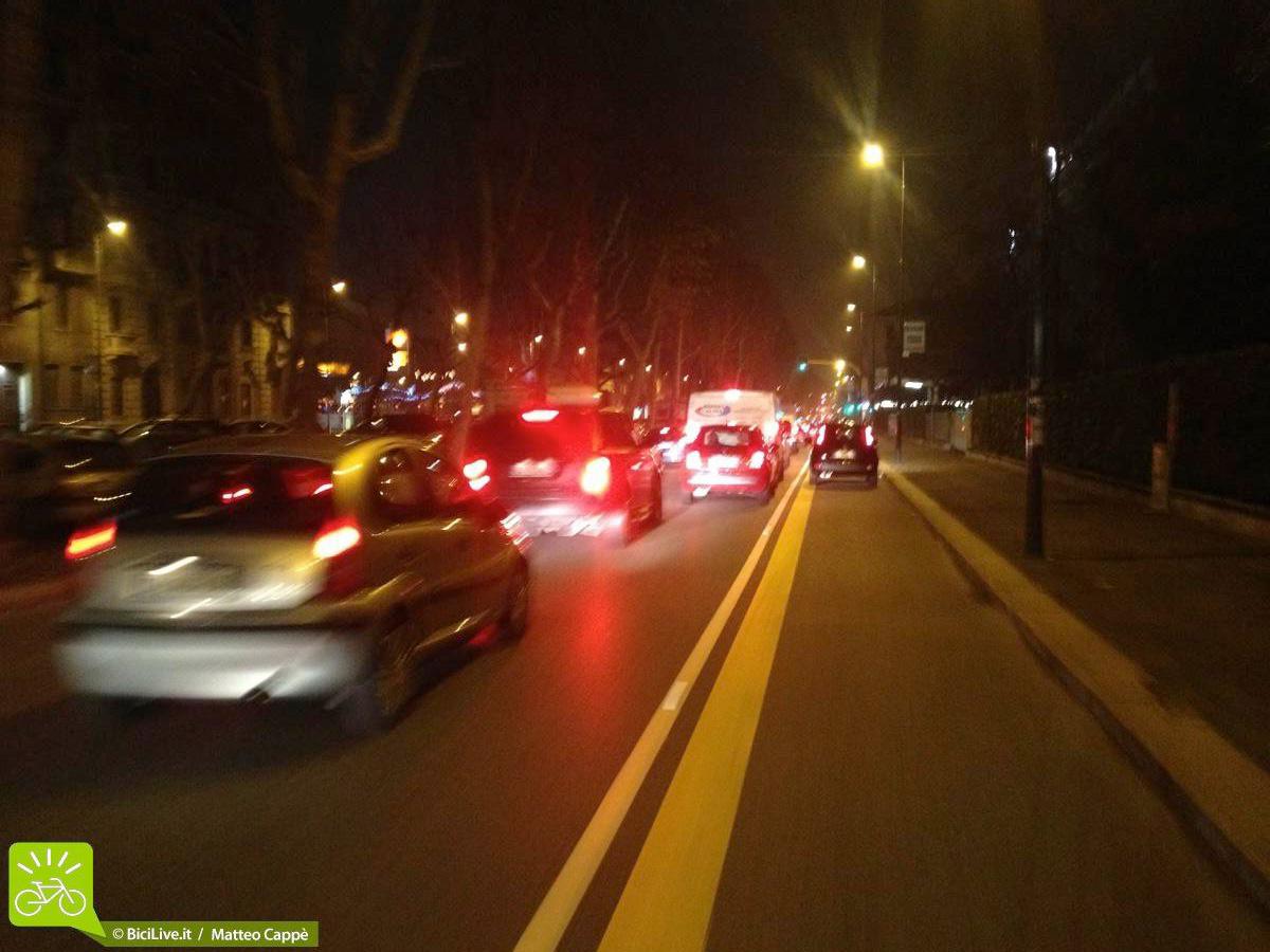 Una strada di Milano trafficata di sera