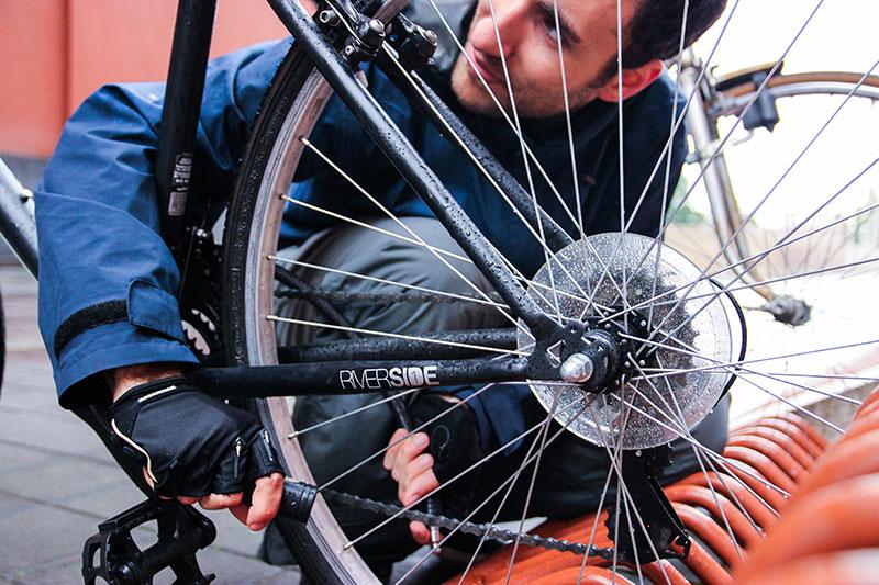Un ciclista lega la sua bicicletta con un antifurto