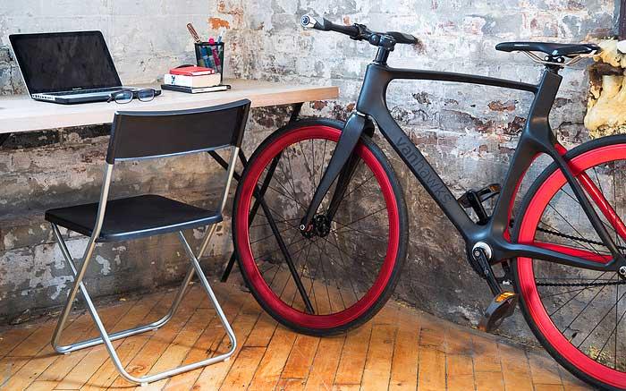La bicicletta da strada Vanhawks Valour accanto a un computer laptop