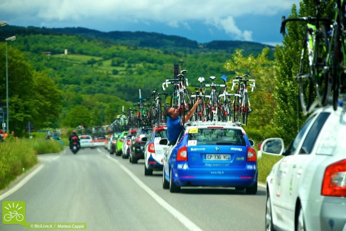 Automobili ammiraglie cariche di biciclette nel corso di una gara ciclistica