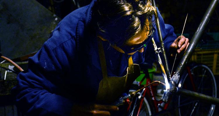 Giovanni mentre usa il saldatore su un futuro telaio di bicicletta