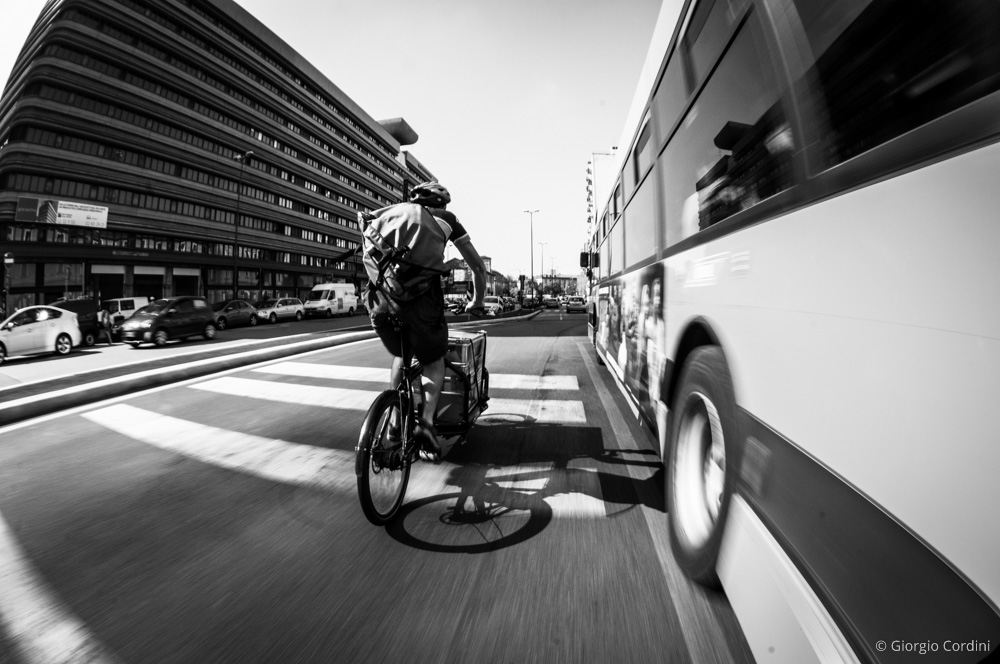 Un corriere in sella a una cargo bike per le vie della città