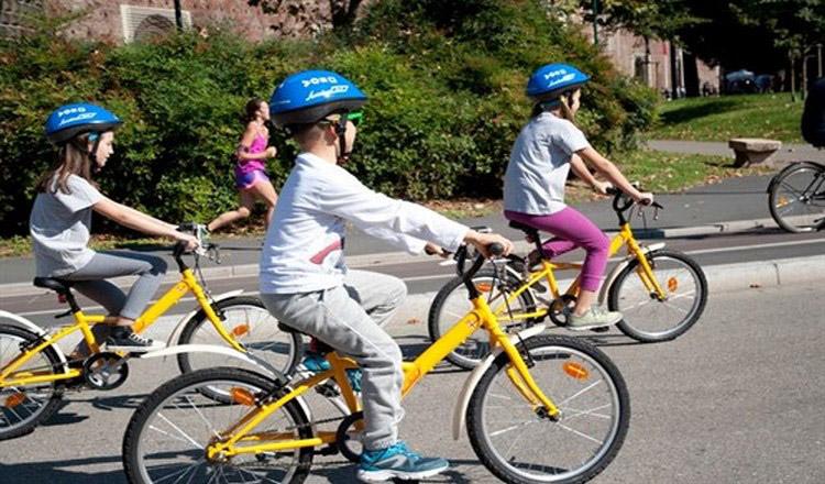 Bambini a Milano che usano il servizio di bike sharing BikeMI Junior in Piazza Castello