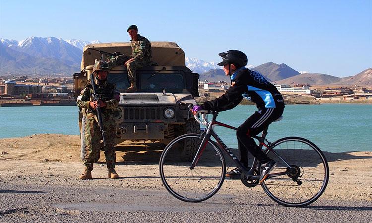 Una ciclista afghana si allena di fronte a dei soldati dalle parti di Kabul