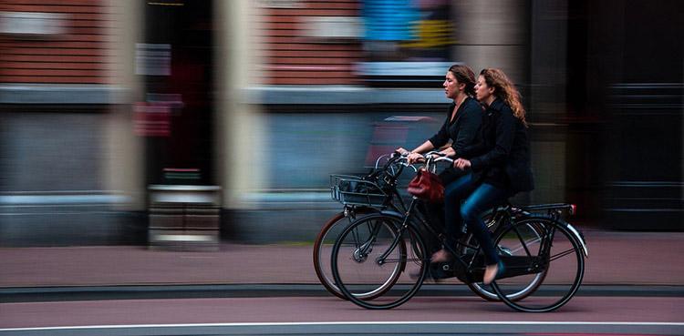 Due donne in bicicletta che vanno a lavorare