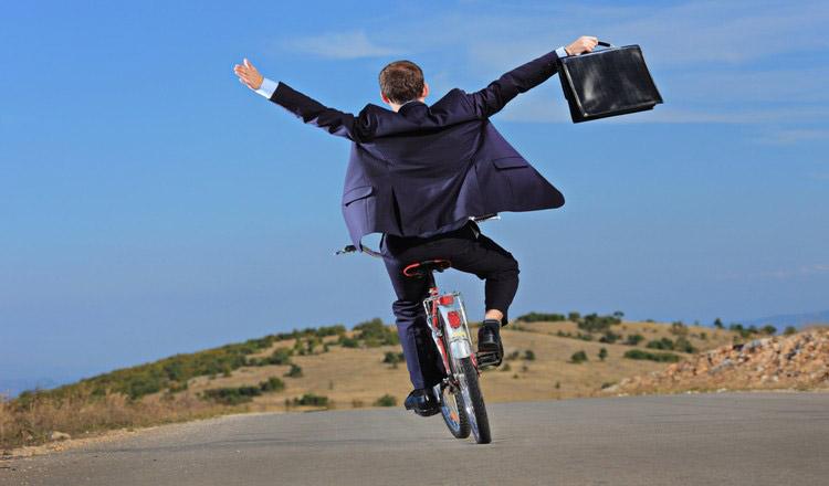 Un impiegato in bicicletta con la borsa da lavoro