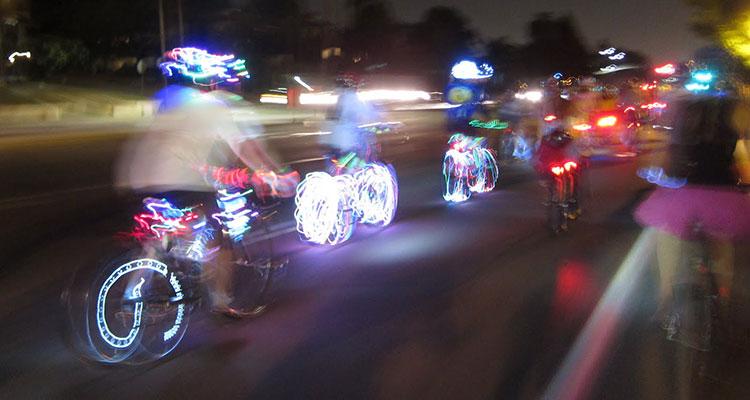 Un gruppo di ciclisti notturni ben visibili grazie a luci e abiti catarifrangenti