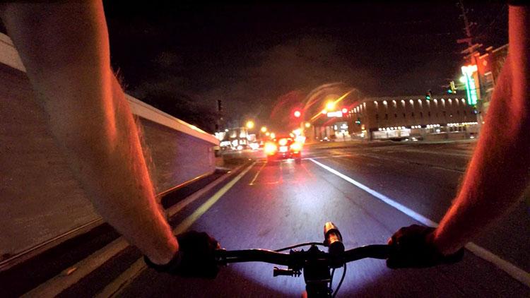 La luce montata sul manubrio di un ciclista notturno illumina la strada