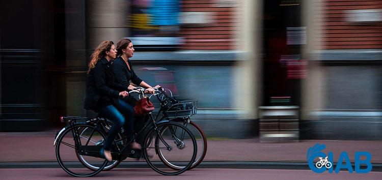 Due donne in sella a due biciclette per le vie della città