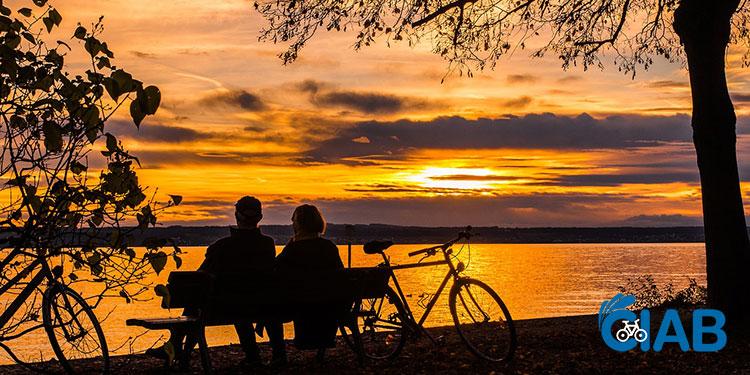 Due turisti in bicicletta si godono il tramonto in riva al lago