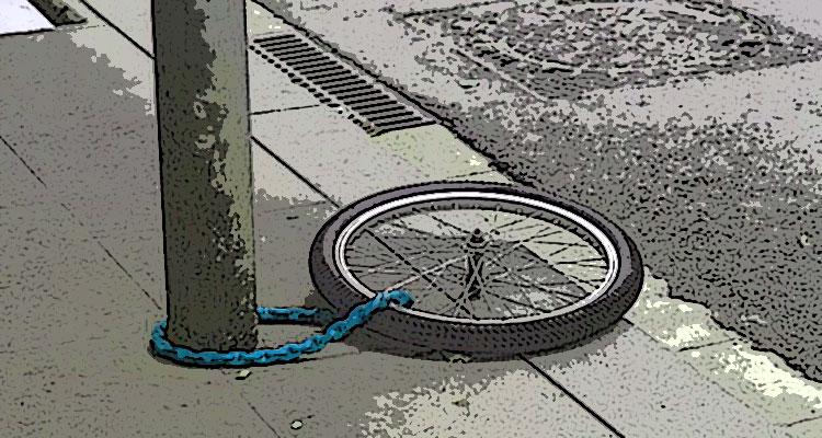 La ruota di una bici rubata legata a un palo da una catena