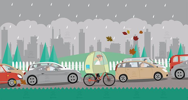 una ciclista pedala nel traffico con una copertura antipioggia