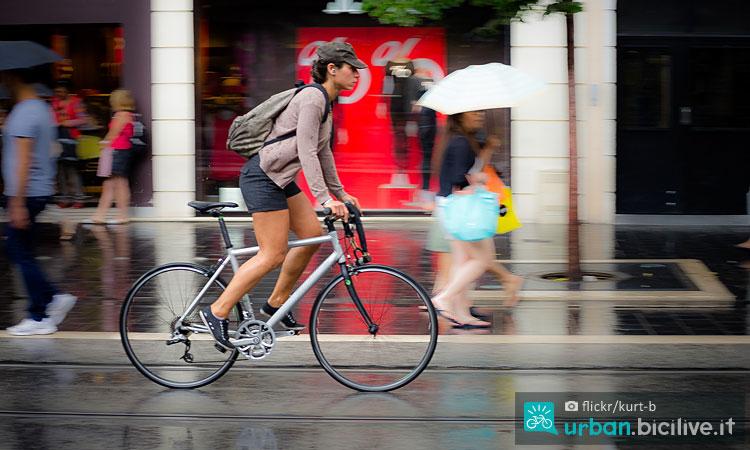 ciclista pedala in città sotto la pioggia