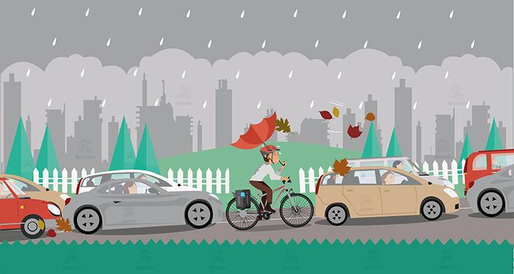 un ciclista nel traffico usa un ombrello per ripararsi dalla pioggia