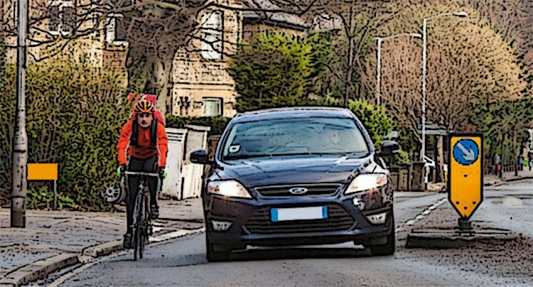 Un'automobile sorpassa una bicicletta