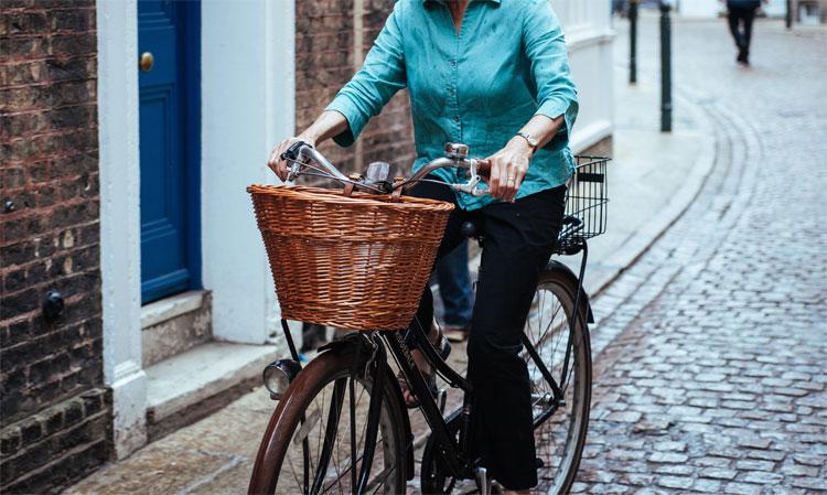 Una donna pedala in sella a una bici con un cestino in vimini