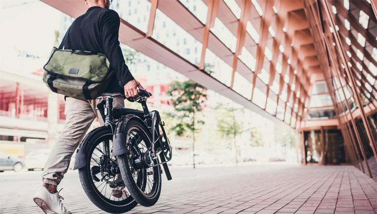 Ciclista a spasso con una bici pieghevole ripiegata