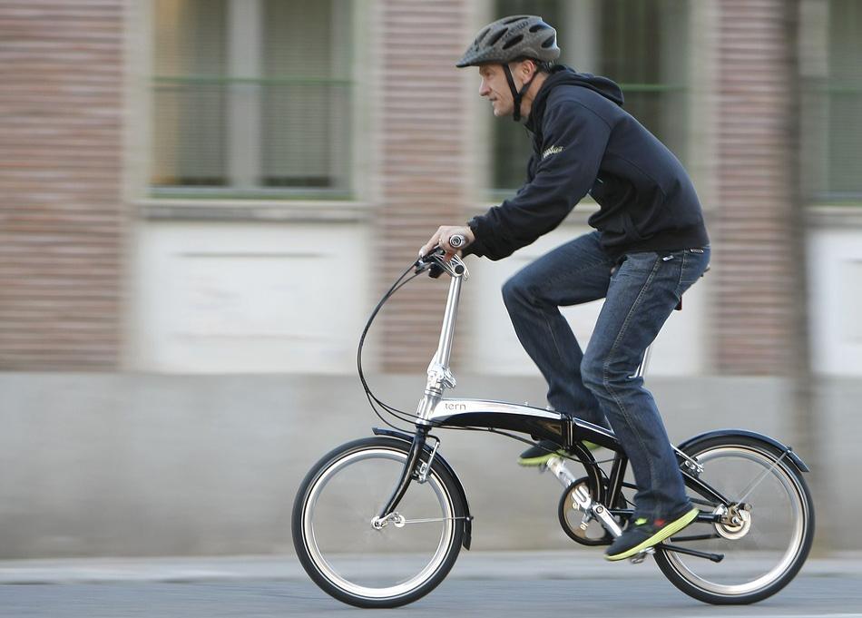 Ciclista urbano pedala per le vie della città in sella a una pieghevole