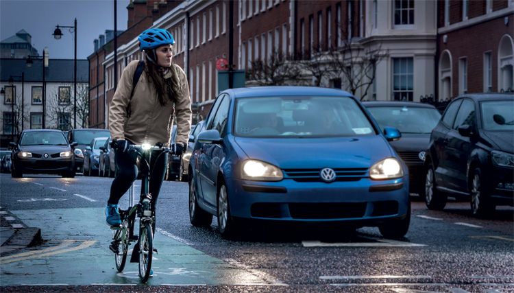 Ciclista in città in sella a una bici pieghevole
