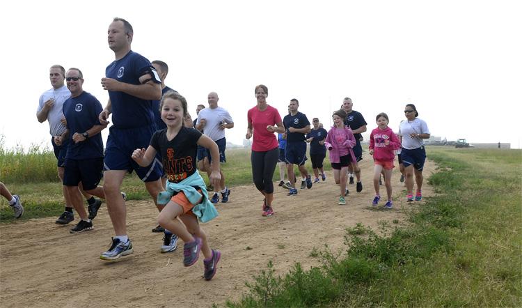 Adulti e bambini di corsa su un sentiero in terra battuta
