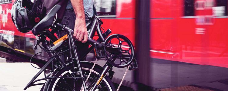 Un viaggiatore che trasporta a mano una bici pieghevole Giant