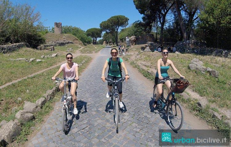 ragazze in bicicletta pedalano sull'Appia Antica
