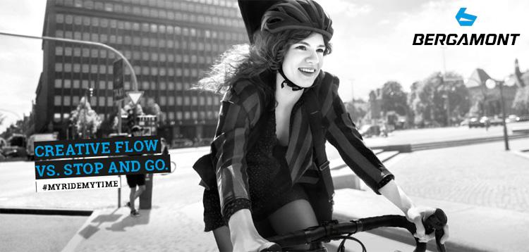 Una ciclista felice pedala in città su una bicicletta Bergamont