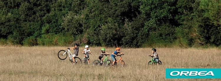 Bambini giocano in un campo in sella a biciclette Orbea
