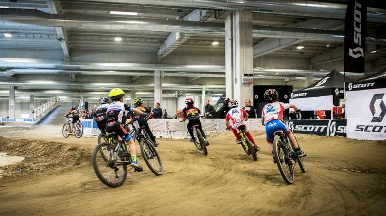 Giovani ciclisti lungo la pista indoor al Travel Outdoor Fest