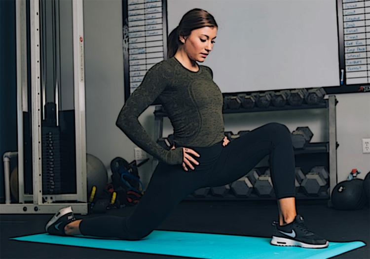 Una donna fa stretching in una palestra casalinga