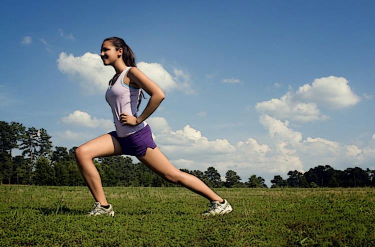 Una giovane donna fa stretching in un parco
