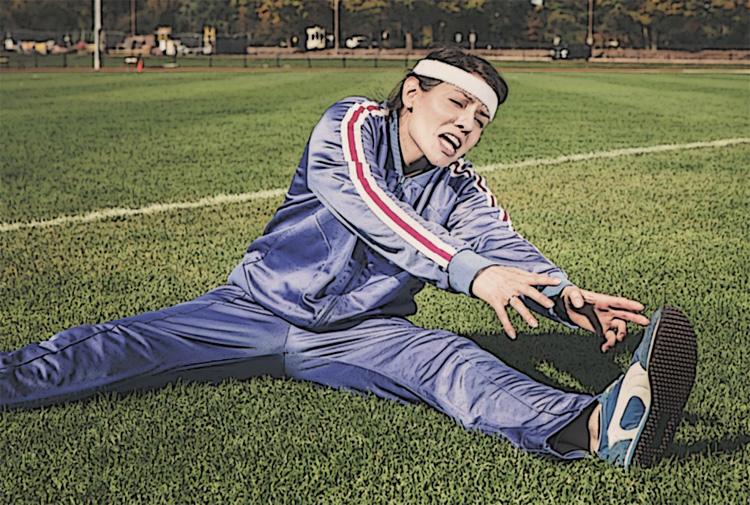 Una donna fa esercizi di stretching al parco