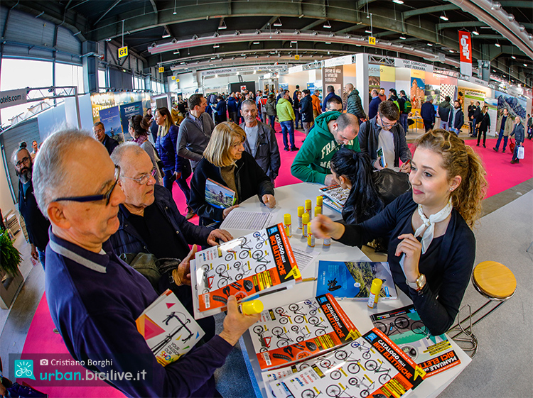 cosmobike 2020 gruppo di visitatori che acquista Il Catalogo delle Bici Elettriche 2020 con bicilive 2019