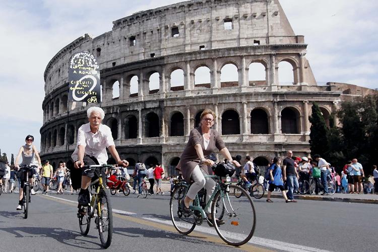 Ciclisti in bicicletta davanti al Colosseo a Roma