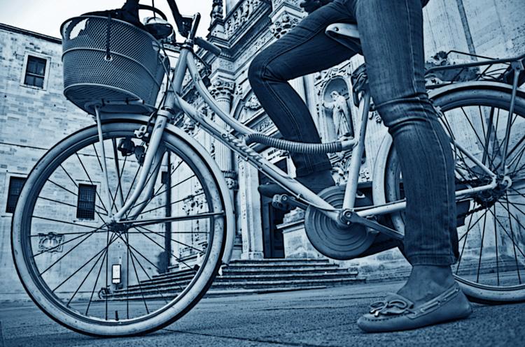 Ciclista di città in sella a bicicletta da passeggio con cestello