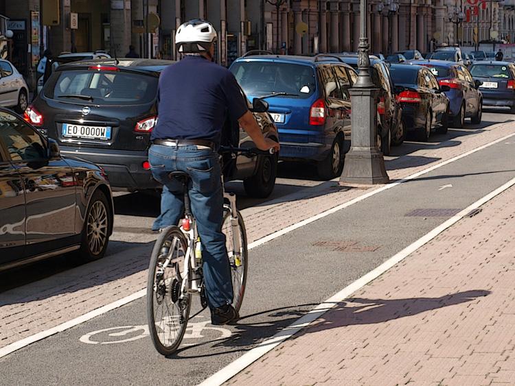 Un ciclista urbano a passeggio lungo una pista ciclabile cittadina