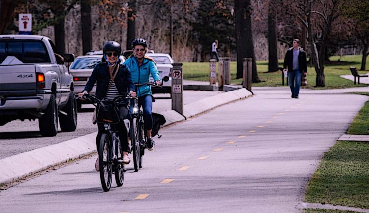 Cicliste a passeggio per la città su pista ciclabile