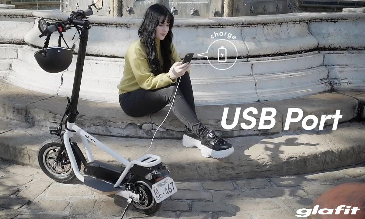 Una donna collega il suo smartphone al monopattino Glafit X-Scooter LOM 2020 tramite porta USB