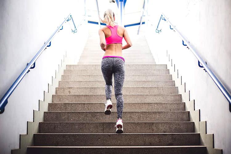 Ragazza fa fitness correndo su per una scalinata