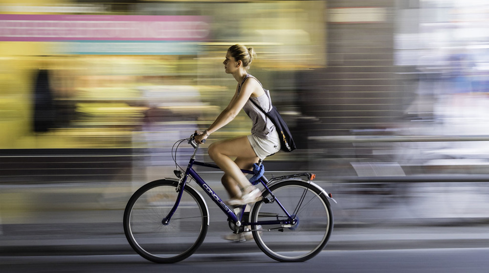 Ragazza va veloce in sella a bicicletta