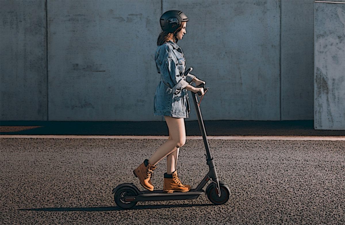 Una ragazza con il casco si sposta su un monopattino elettrico