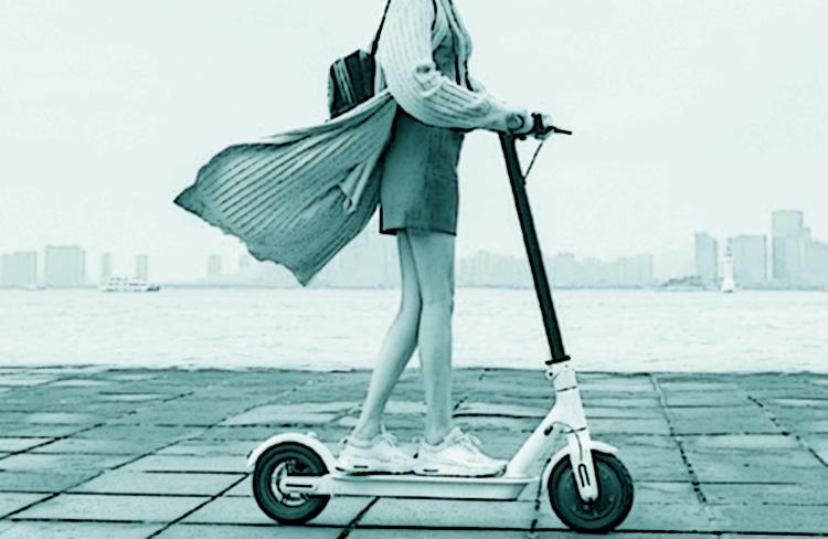 Una ragazza con la gonna si sposta su un monopattino elettrico