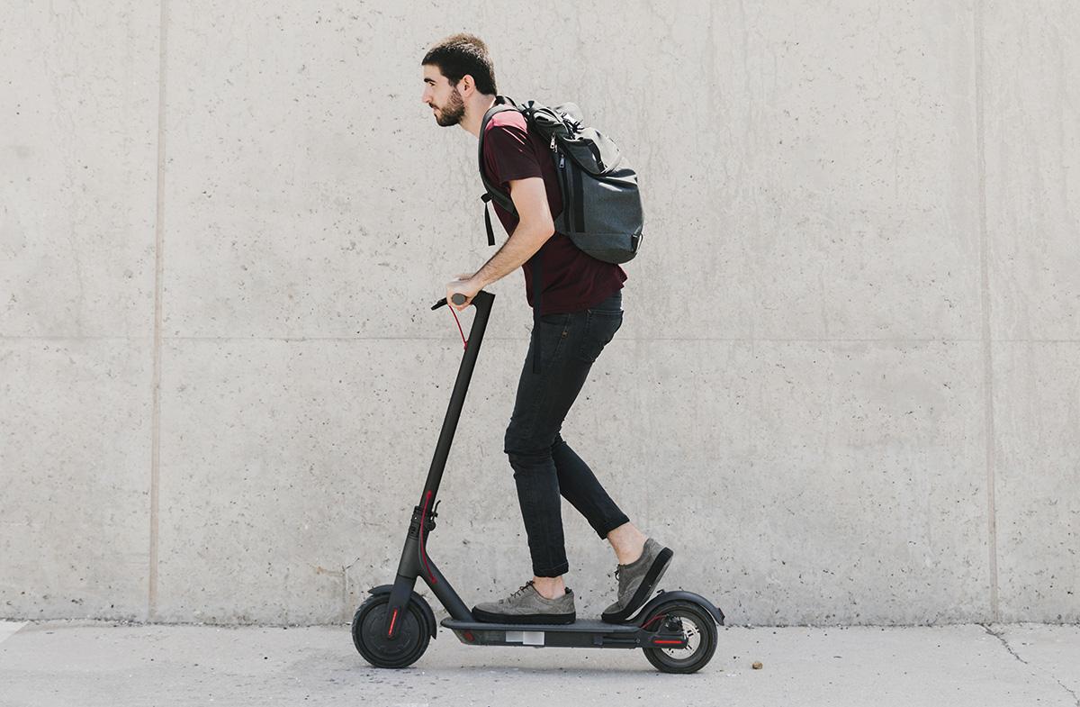 Un ragazzo che viaggia con il monopattino elettrico