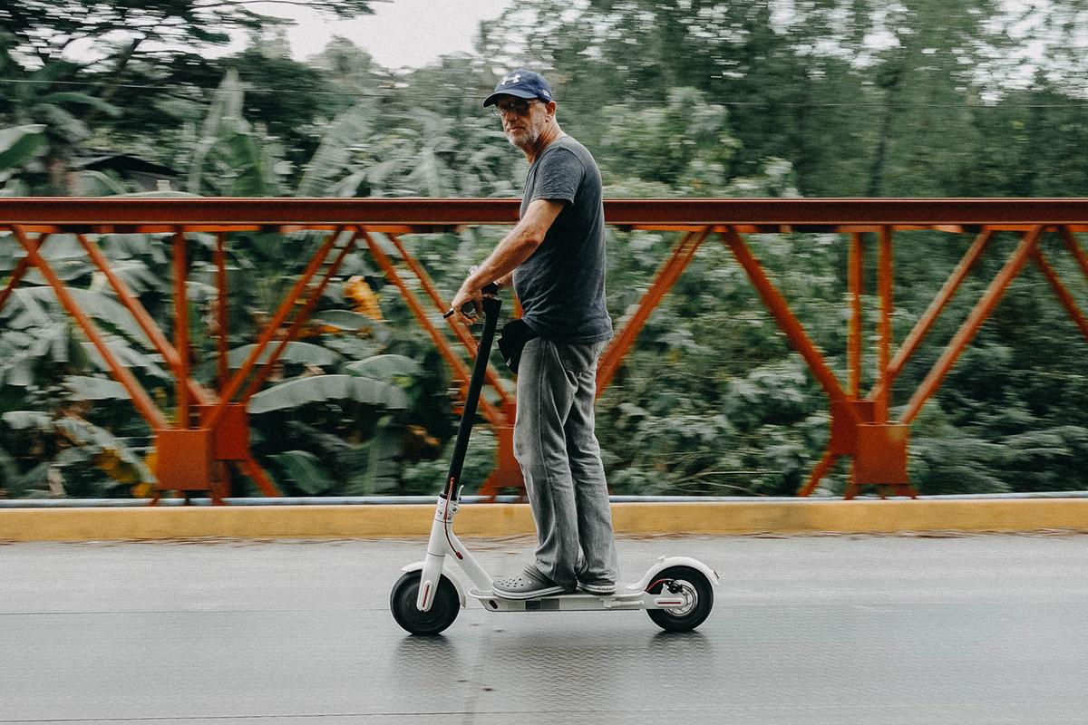 Un uomo che guida il monopattino elettrico sulla pista ciclabile