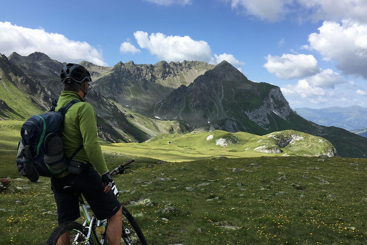 uomo di spalle in bici guarda il paesaggio