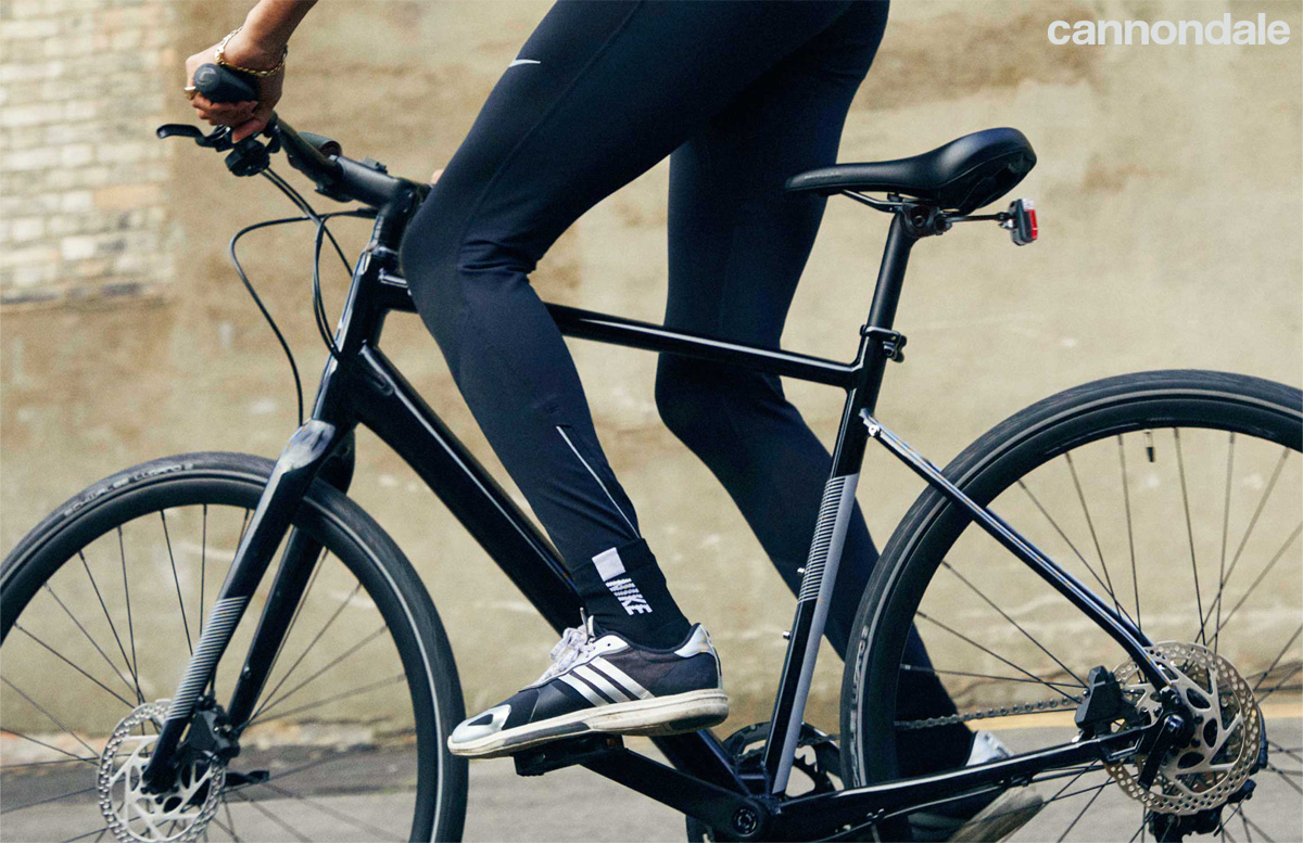 Ciclista pedala in piedi su una bici Cannondale Quick 1
