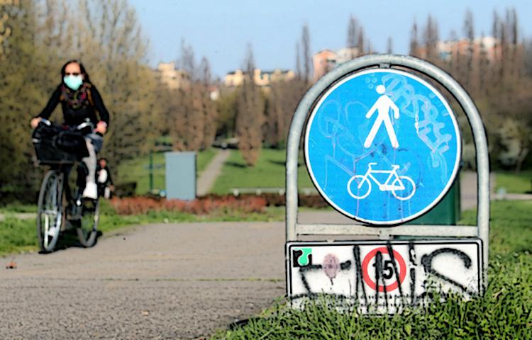Ciclista donna pedala in un parco cittadino indossando una mascherina anti-contagio