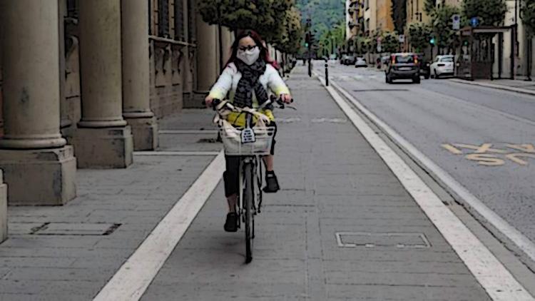 Ciclista donna si sposta in bici per la città indossando una mascherina